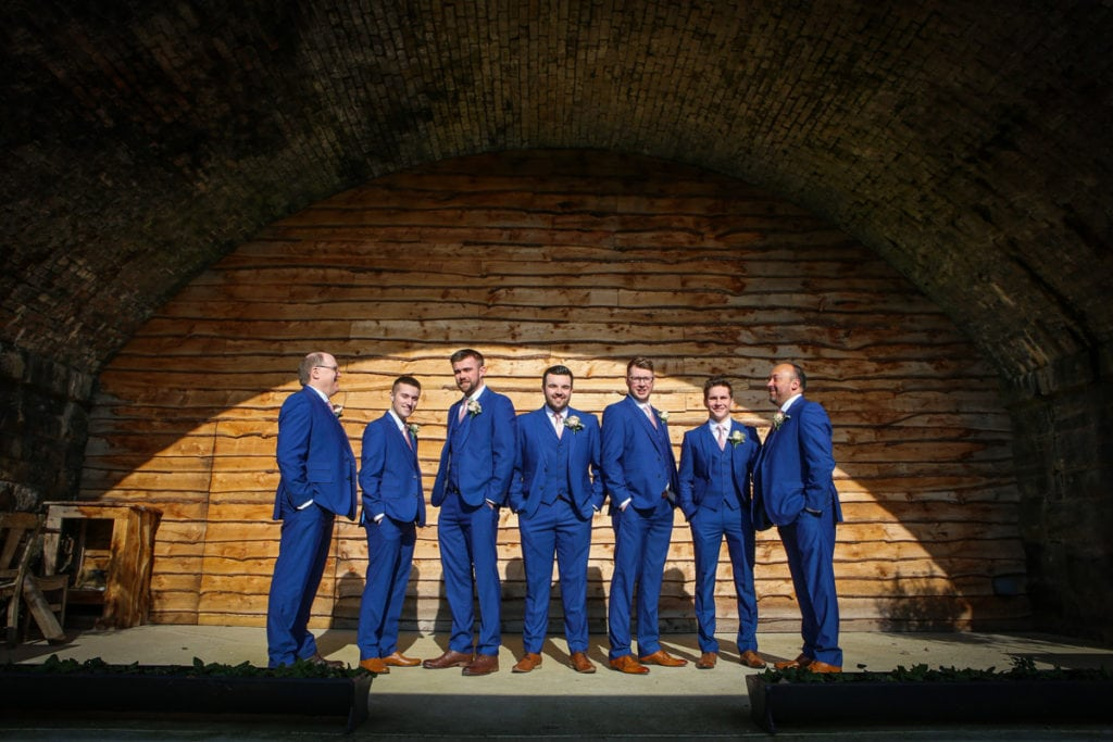 Groomsmen stood under arch
