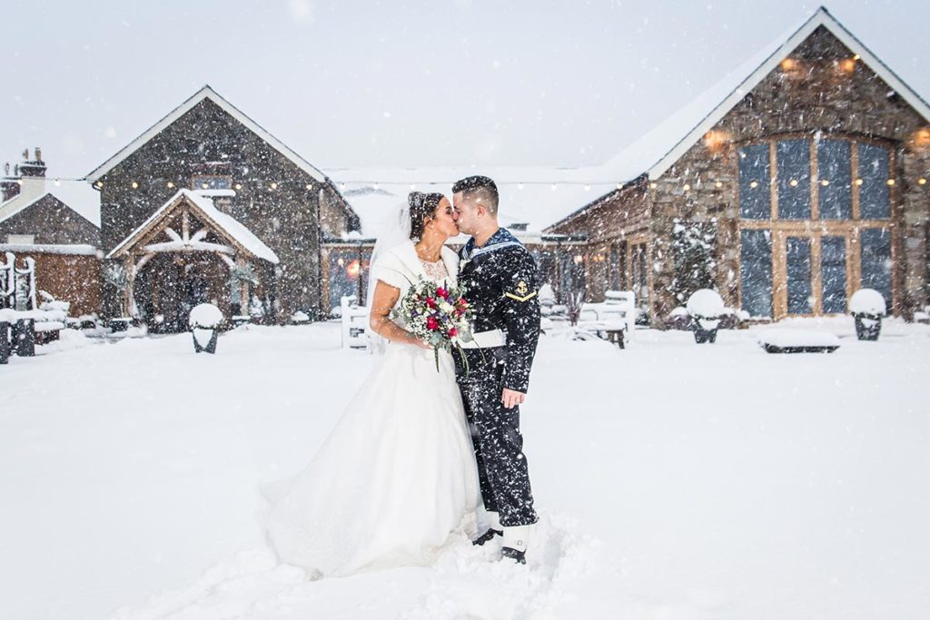 Bride and groom stood outside a snowy venue