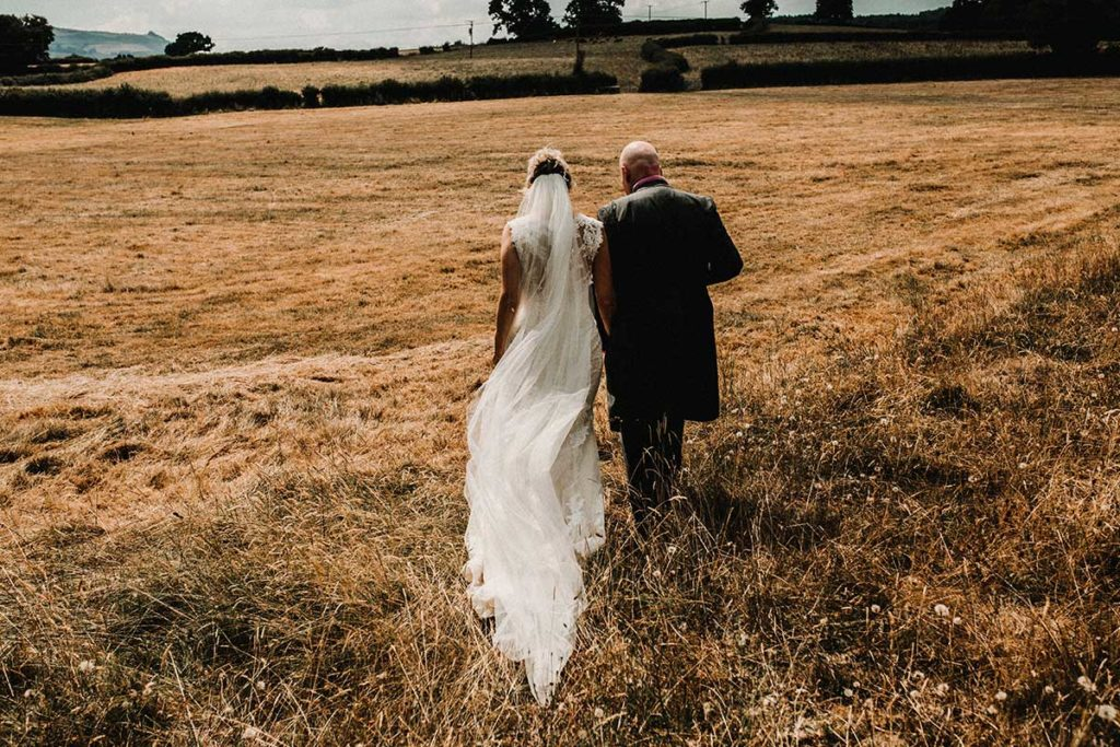 bride and groom walking through a field