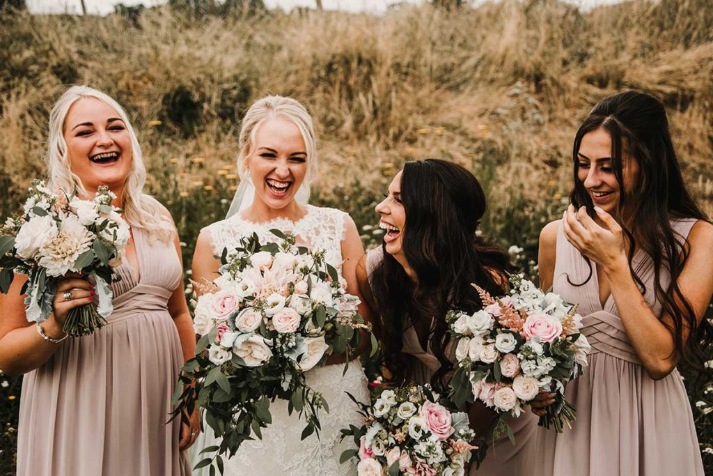 Bridesmaids hold bouquets of flowers