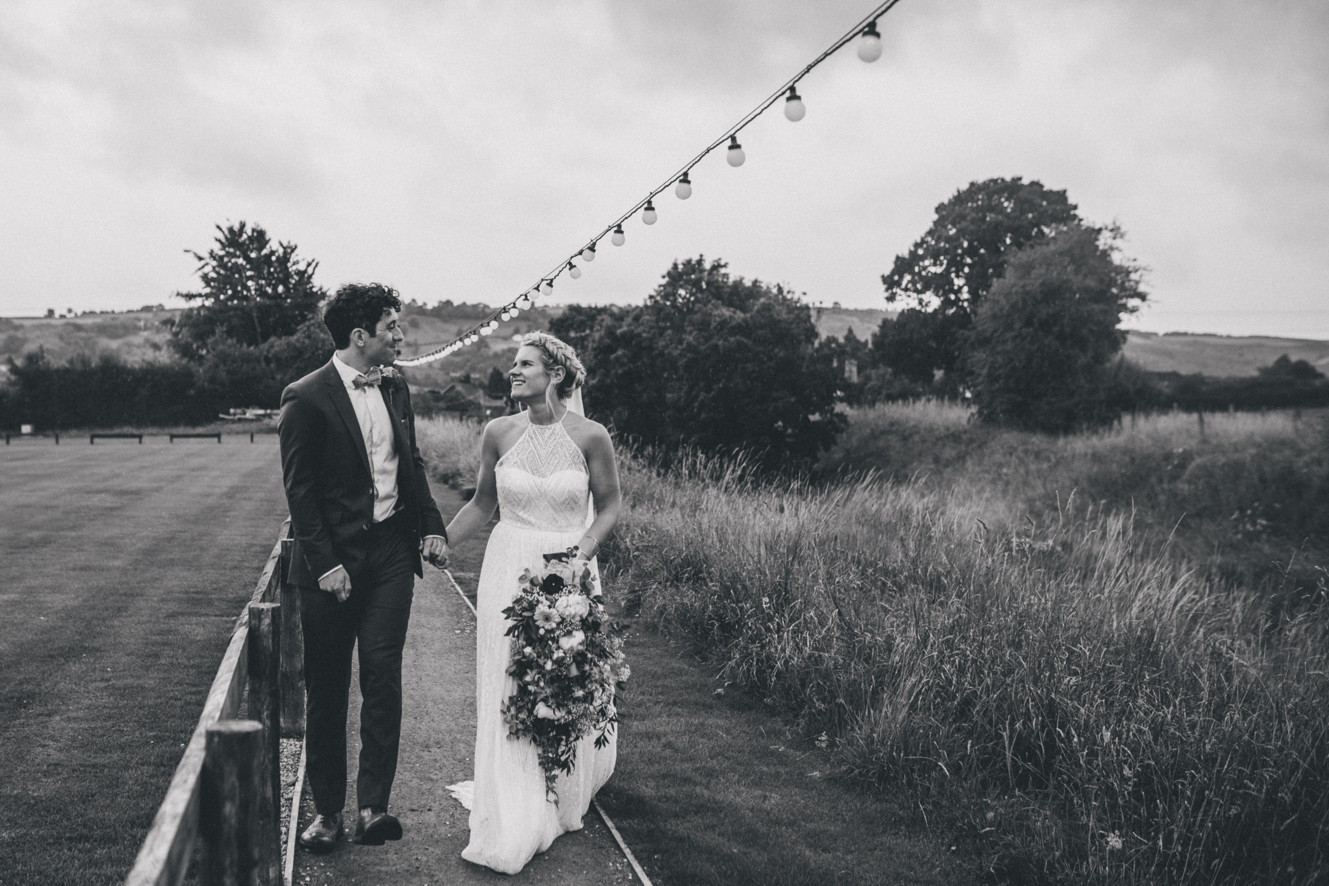 A boho floral wedding couple strolling the walkway underneath our string lights here at Tower Hill Barns with Claire Penn Photography