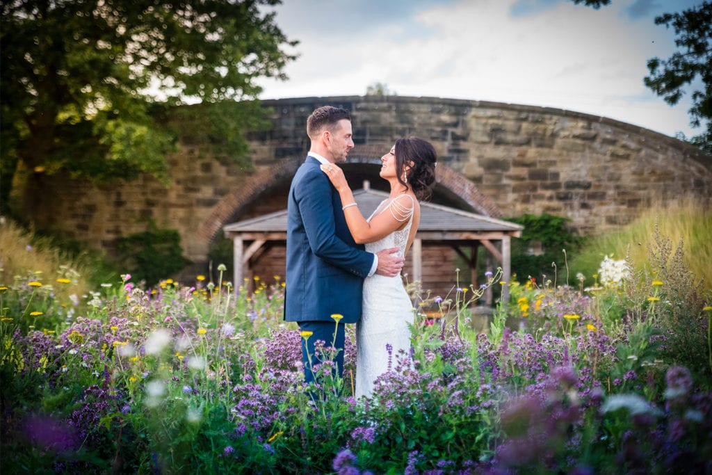 Couple having wedding photos in the wildflower meadow during the summer at Tower Hill Barns