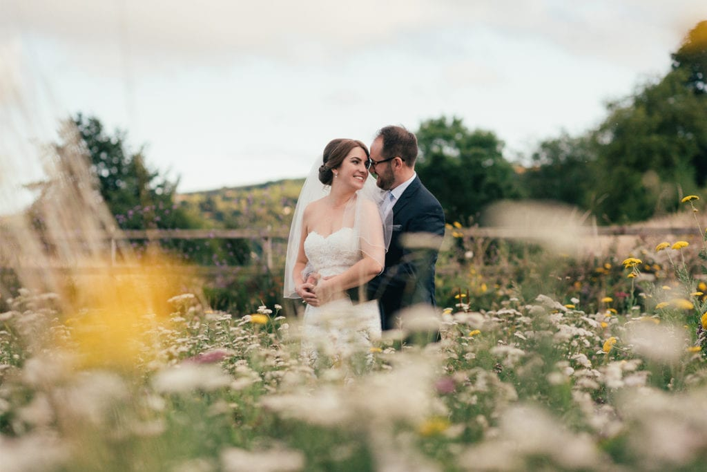 Newlywed couple Louise and Andy in the wildflower meadow in the summer of 2018 at Tower Hill Barns North Wales